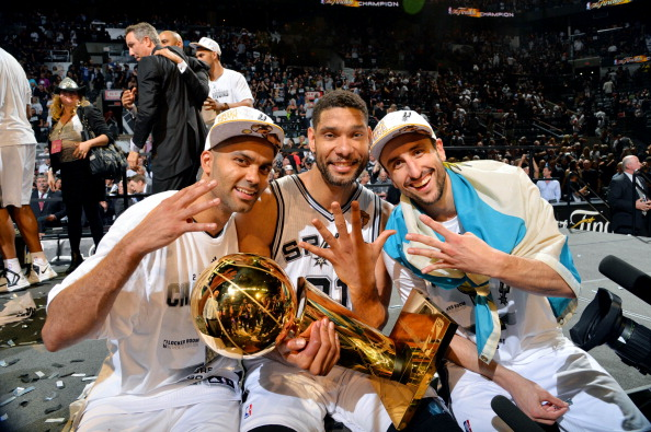 SAN ANTONIO, TX - JUNE 15: Manu Ginobili #20, Tony Parker #9, and Tim Duncan #21 of the San Antonio Spurs celebrate with the Larry O'Brien trophy after defeating the Miami Heat to win the 2014 NBA Finals in Game Five of the 2014 NBA Finals on June 15, 2014 at AT&T Center in San Antonio, Texas. NOTE TO USER: User expressly acknowledges and agrees that, by downloading and or using this photograph, User is consenting to the terms and conditions of the Getty Images License Agreement. Mandatory Copyright Notice: Copyright 2014 NBAE (Photo by Jesse D. Garrabrant/NBAE via Getty Images)