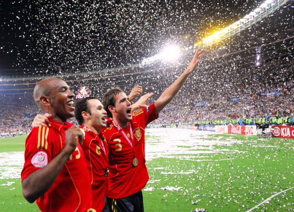 (From L) Spanish midfielders Marcos Senna and Andres Iniesta and defender Fernando Navarro celebrate with supporters after winning the Euro 2008 championships final football match over Germany on June 29, 2008 at Ernst-Happel stadium in Vienna, Austria. Spain ended their 44-year wait for a major international title with a 1-0 victory over Germany at the Euro 2008 final. AFP PHOTO / JOE KLAMAR -- MOBILE SERVICES OUT -- (Photo credit should read JOE KLAMAR/AFP/Getty Images)