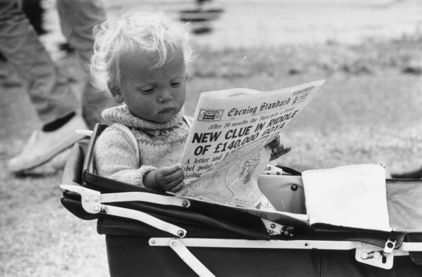 July 1962: Young Roy Turner at Henley regatta prefers to read the paper in his pram. (Photo by Evening Standard/Getty Images)