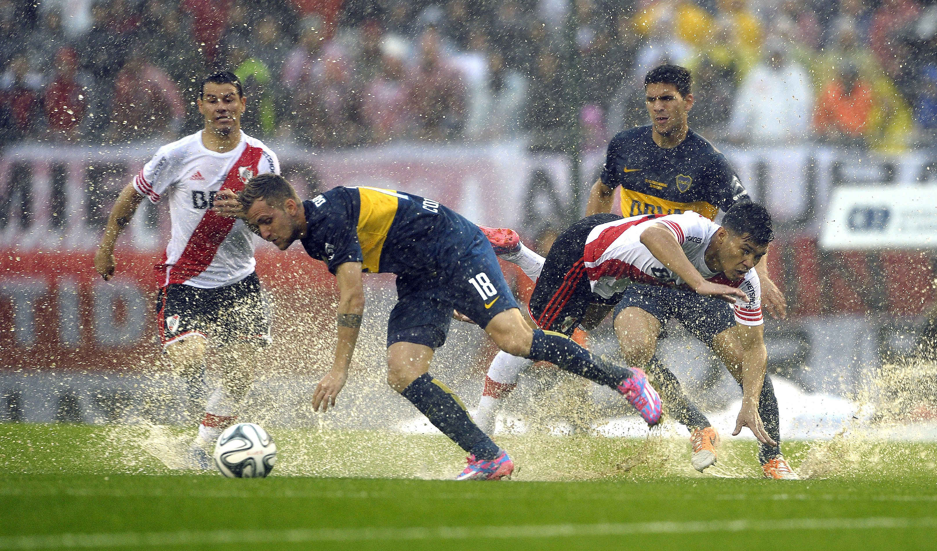 Boca Juniors' midfielder Nicolas Colazo (C-L) vies for the ball with River Plate's forward Teofilo Gutierrez (C-R) during their Argentina First Division football match, at the Monumental stadium in Buenos Aires, Argentina, on October 5, 2014. AFP PHOTO / Alejandro PAGNI (Photo credit should read ALEJANDRO PAGNI/AFP/Getty Images)