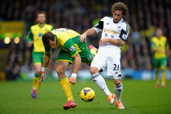 NORWICH, ENGLAND - DECEMBER 15:  Johan Elmander of Norwich battles with Jose Canas of Swansea during the Barclays Premier League match between Norwich City and Swansea City at Carrow Road on December 15, 2013 in Norwich, England.  (Photo by Christopher Lee/Getty Images)