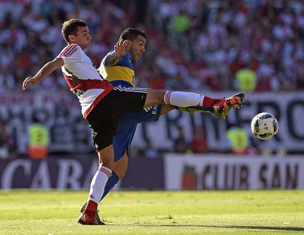 Boca Juniors' forward Carlos Tevez (R) vies for the ball with River Plate's defender Emanuel Mammana during their Argentine first division football match at the Monumental stadium in Buenos Aires, Argentina, on March 6, 2016. AFP PHOTO / JUAN MABROMATA / AFP / JUAN MABROMATA (Photo credit should read JUAN MABROMATA/AFP/Getty Images)