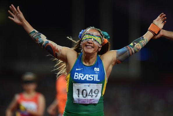 LONDON, ENGLAND - SEPTEMBER 05: Terezinha Guilhermina of Brazil celebrates as she wins gold with guide Guilherme Soares de Santana (not pictured) in the Women's 100m T11 Final on day 7 of the London 2012 Paralympic Games at Olympic Stadium on September 5, 2012 in London, England. (Photo by Gareth Copley/Getty Images)